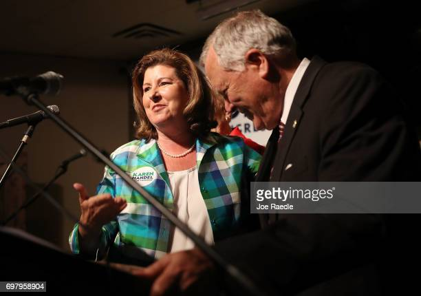 Republican candidate Karen Handel stands with Georgia Governor Nathan Deal as he introduces her to speak during a campaign stop at Houck's Grille as...