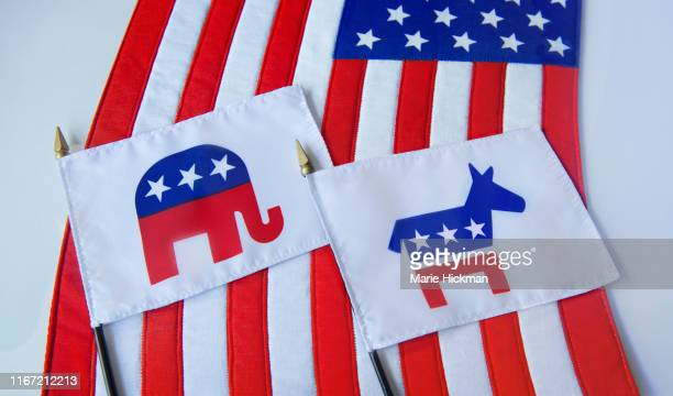 republican elephant and democratic donkey political party symbols on two small flags laying on the american flag. - democratic party usa stock pictures, royalty-free photos & images