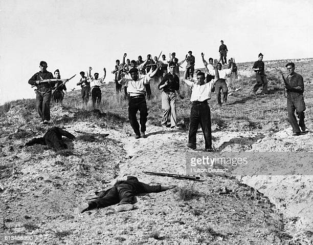 Republican fighters entrenched on the crest of a hill on the Somo Sierra front in northern Spain surrender as they are captured by Nationalist troops...
