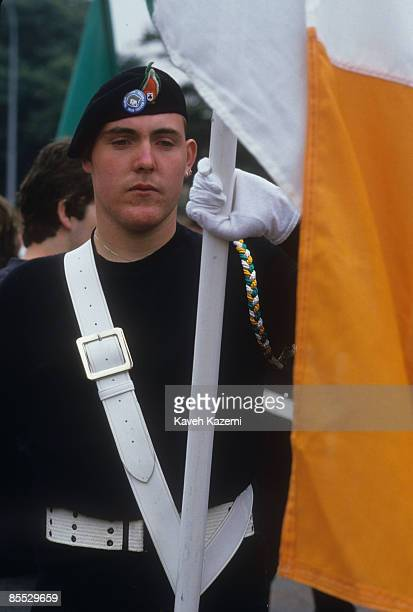 A Republican flag holder wearing a black outfit and a beret during a march in Falls Road west Belfast 9th August 1986 He wears a cap badge depicting...