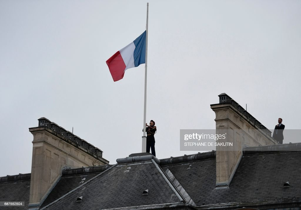 A Republican guard flies the French flag at half mast at the Elysee presidential Palace in Paris on May 24, 2017 in tribute to the victims of the May 22 terror attack at the Ariana Grande concert in Manchester that killed 22 and injured dozens. Police on May 23 named a young man -- reportedly British-born of Libyan descent -- as the suspect behind a suicide bombing that ripped into young fans at a concert in Manchester, as the Islamic State group claimed responsibility for Britain's deadliest terror attack in over a decade. /