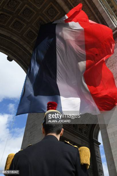 A Republican guard stands under a giant French flag fluttering at the Arc of Triomphe monument after the Emmanuel Macron's formal inauguration...