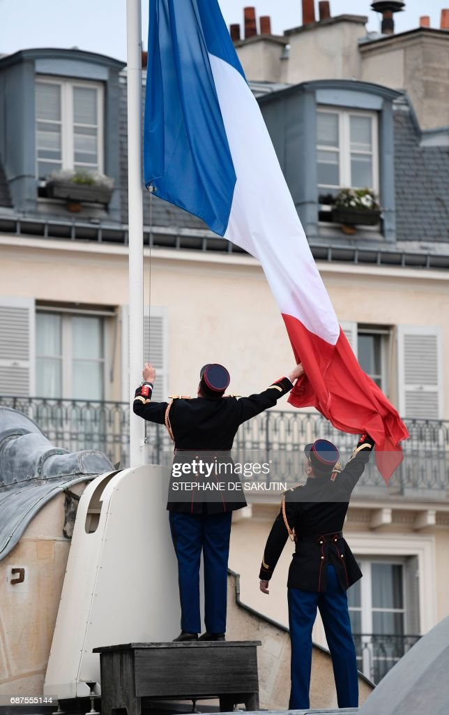 Republican guards fly the French flag at half mast at the Elysee presidential Palace in Paris on May 24, 2017 in tribute to the victims of the May 22 terror attack at the Ariana Grande concert in Manchester that killed 22 and injured dozens. Police on May 23 named a young man - reportedly British-born of Libyan descent - as the suspect behind a suicide bombing that ripped into young fans at a concert in Manchester, as the Islamic State group claimed responsibility for Britain's deadliest terror attack in over a decade. /