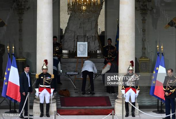 TOPSHOT Republican guards stand next to a portrait of Jacques Chirac displayed at the Elysee presidential palace in Paris on September 27 2019 as...