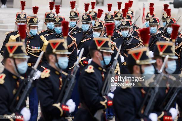 Republican guards wearing face masks take part in a welcoming ceremony for the Romanian prime minister in the courtyard of the Invalides in Paris on...