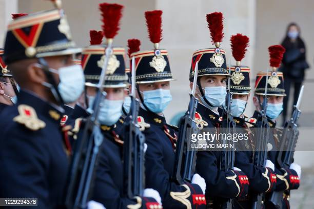 Republican guards wearing face masks take part in a welcoming ceremony for the Romanian prime minister in the courtyard of the Invalides in Paris, on...