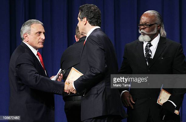 Republican gubernatorial nominee Carl Paladino shakes hands with Democratic gubernatorial candidate Andrew Cuomo as Jimmy McMillan of the Rent is 2...