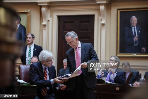 Republican Majority Leader of the Senate of Virginia Tommy Norment confers with a colleague on the Senate floor at the Virginia State Capitol...