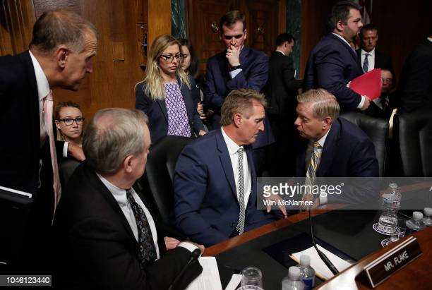 Republican members of the Senate Judiciary Committee surround Sen Jeff Flake after he announced he was in favor of a delay in the Kavanaugh...