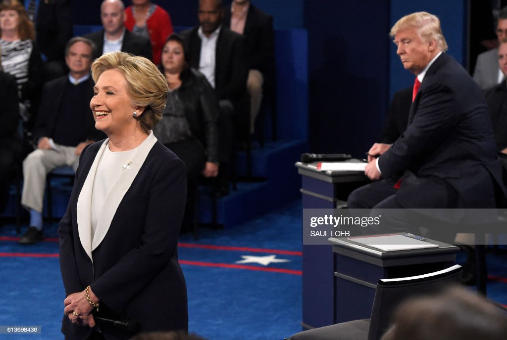 TOPSHOT - Republican nominee Donald Trump (R) looks at Democratic nominee Hillary Clinton as she speaks during the second presidential debate at Washington University in St. Louis, Missouri on October 9, 2016. /