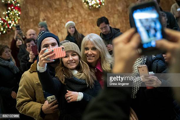 Republican political strategist Kellyanne Conway takes a selfie photo with visitors in the lobby at Trump Tower, December 16, 2016 in New York City....