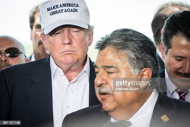 Republican Presidential candidate and business mogul Donald Trump listens as Laredo City Manager Jesus Olivares center and Laredo mayor Pete Saenz...