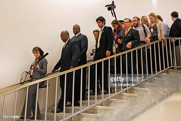 Republican presidential candidate and former CEO of Godfather's Pizza Herman Cain is pursued down a flight of stairs by journalists after...