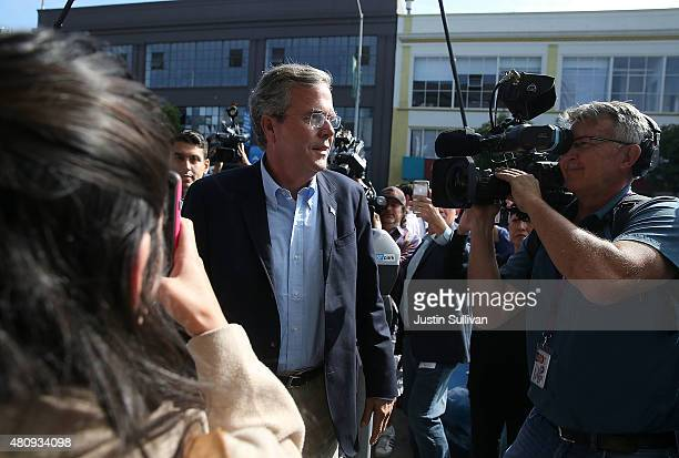 Republican presidential candidate and former Florida governor Jeb Bush walks through a crowd of media as he arrives at Thumbtack on July 16 2015 in...
