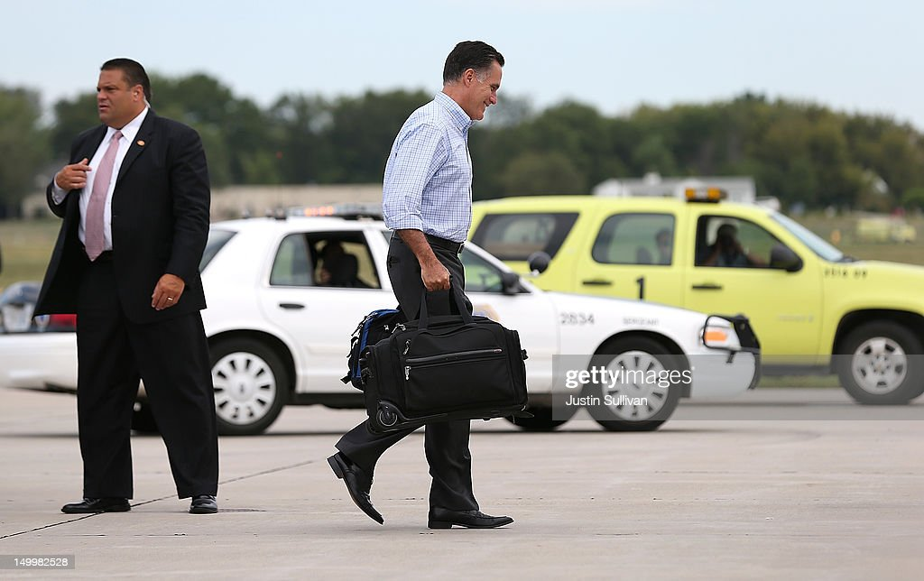 Republican presidential candidate and former Massachusetts Gov. Mitt Romney carries bags as he walks to his campaign plane at Des Moines International Airport on August 8, 2012 in Des Moines, Iowa. Mitt Romney is campaigning in Iowa before traveling to New Jersey and New York for fundraising events.