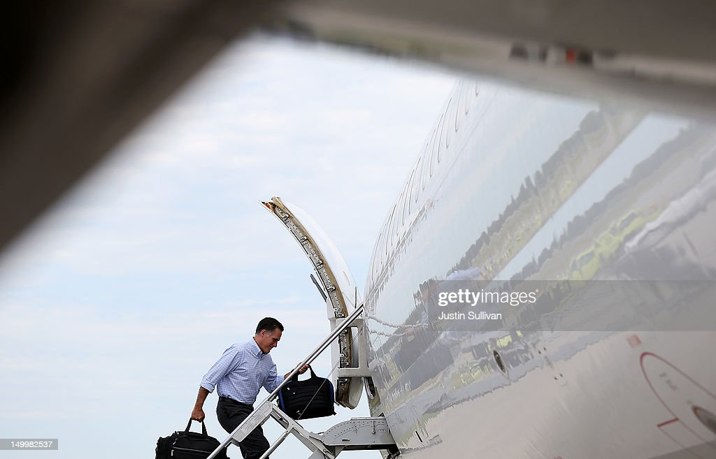 Republican presidential candidate and former Massachusetts Gov. Mitt Romney carries bags as he boards his campaign plane at Des Moines International Airport on August 8, 2012 in Des Moines, Iowa. Mitt Romney is campaigning in Iowa before traveling to New Jersey and New York for fundraising events.