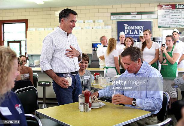Republican presidential candidate and former Massachusetts Governor Mitt Romney eats ice cream with Ohio Governor John Kasich during a campaign rally...