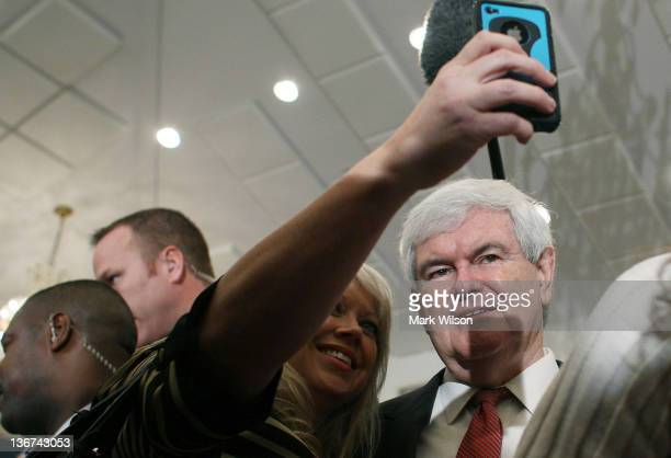 Republican presidential candidate and former Speaker of the House Newt Gingrich poses for A pictures with A supporter during a campaign event at the...