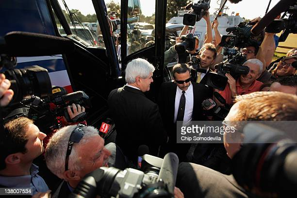Republican presidential candidate and former Speaker of the House Newt Gingrich is surrounded by journalists and security guards as he campaigns on...