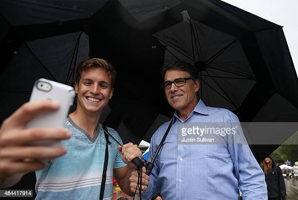 Republican presidential candidate and former Texas Gov Rick Perry takes a selfie with a fairgoer as he tours the Iowa State Fair on August 18 2015 in...