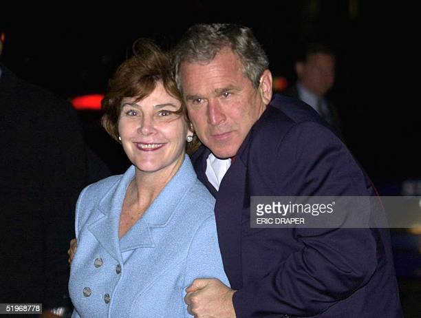 Republican presidential candidate and Texas Governor George W Bush playfully poses with his wife Laura at his arrival in Detroit MI after a flight...