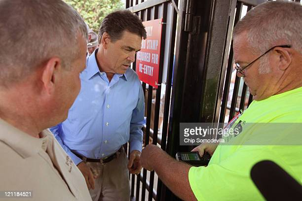 Republican presidential candidate and Texas Governor Rick Perry has his ticket to the Iowa State Fair scanned as he arrives August 15 2011 in Des...