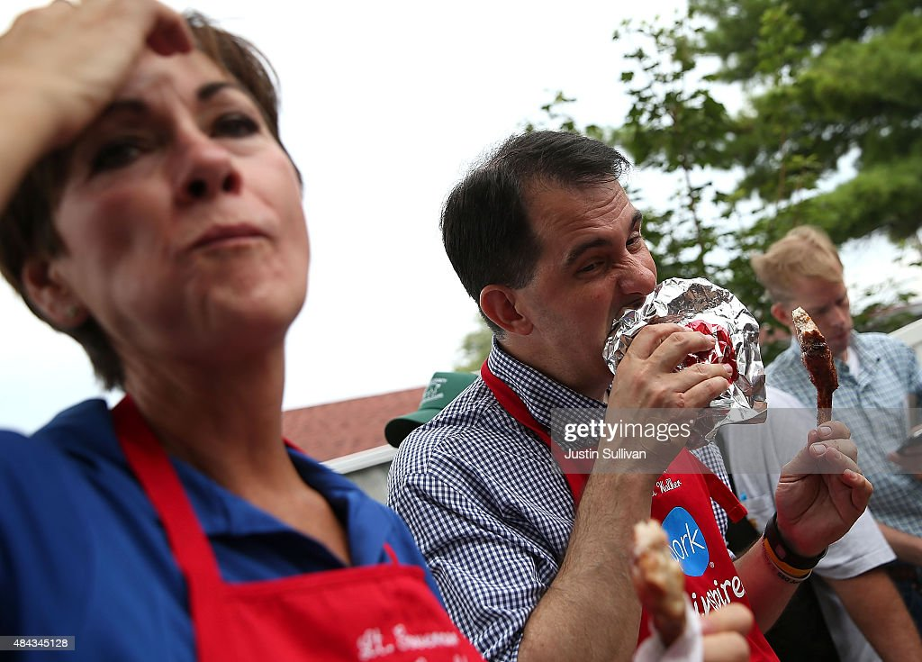 Republican presidential candidate and Wisconsin Gov. Scott Walker (R) bites into a pork chop at the Iowa Pork Producers Pork Tent as Iowa Lt. Gov. Kim Reynolds (R) looks on during the Iowa State Fair on August 17, 2015 in Des Moines, Iowa. Presidential candidates are addressing attendees at the Iowa State Fair on the Des Moines Register Presidential Soapbox stage and touring the fairgrounds. The State Fair runs through August 23.