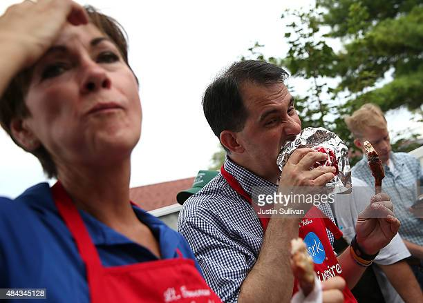 Republican presidential candidate and Wisconsin Gov Scott Walker bites into a pork chop at the Iowa Pork Producers Pork Tent as Iowa Lt Gov Kim...