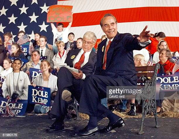 Republican presidential candidate Bob Dole turns and looks over his shoulder at cheering supporters as he and his runningmate Jack Kemp wait for...
