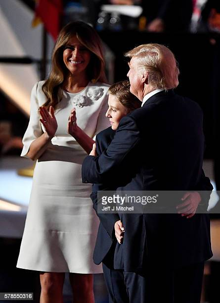 Republican presidential candidate Donald embraces his son Barron Trump after delivering his speech as Melania Trump looks on during the fourth day of...