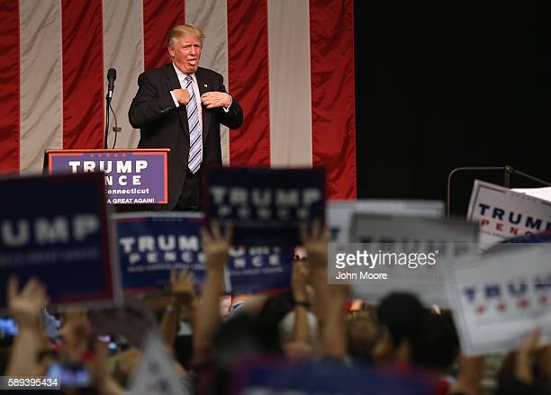 Republican Presidential candidate Donald Trump acknowledges the high temperature after addressing supporters on August 13 2016 in Fairfield...