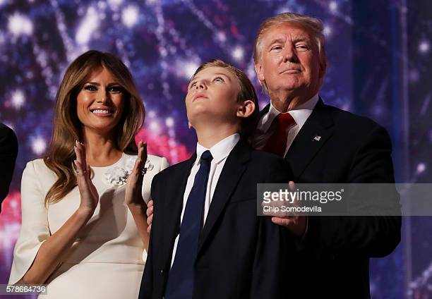 Republican presidential candidate Donald Trump embraces his son Barron Trump as his wife Melania Trump looks on at the end of the Republican National...