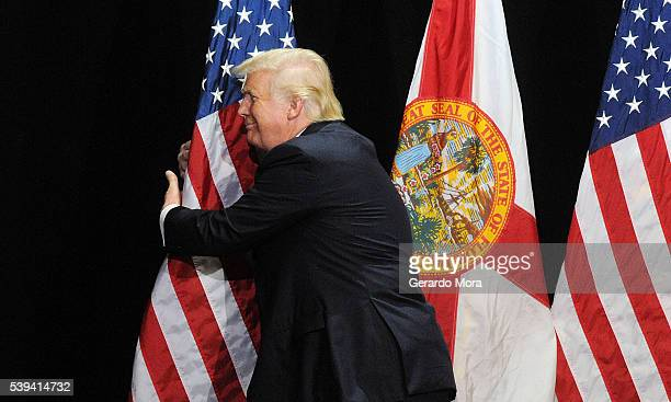 Republican presidential candidate Donald Trump embraces the United States flag during a campaign rally at the Tampa Convention Center on June 11 2016...