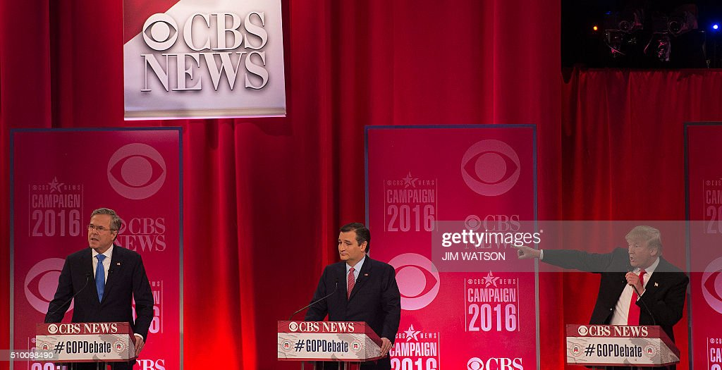 TOPSHOT - Republican presidential candidate Donald Trump (R) gestures towards fellow candidate Jeb Bush (L) as they argue through candidate Ted Cruz (C) during the CBS News Republican Presidential Debate in Greenville, South Carolina, February 13, 2016. / AFP / JIM