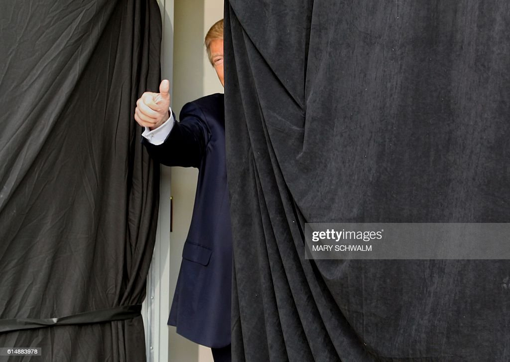 TOPSHOT - Republican presidential candidate Donald Trump gives a thumbs up from behind the curtain before taking the stage at an event on October 15, 2016 in Portsmouth, New Hampshire. Trump charged on Saturday that 'corrupt' media were seeking to rig November's presidential election in favor of his Democratic rival Hillary Clinton. / AFP / Mary Schwalm