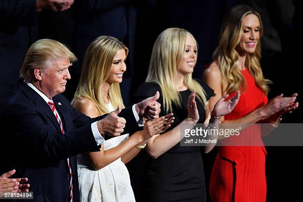 Republican presidential candidate Donald Trump gives two thumbs up as Ivanka Trump Tiffany Trump and Lara Yunaska stand and cheer for Eric Trump as...