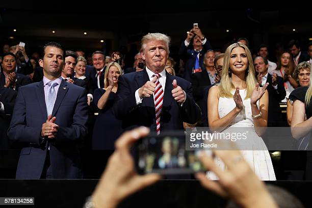 Republican presidential candidate Donald Trump gives two thumbs up as Donald Trump Jr and Ivanka Trump stand and cheer for Eric Trump as he delivers...
