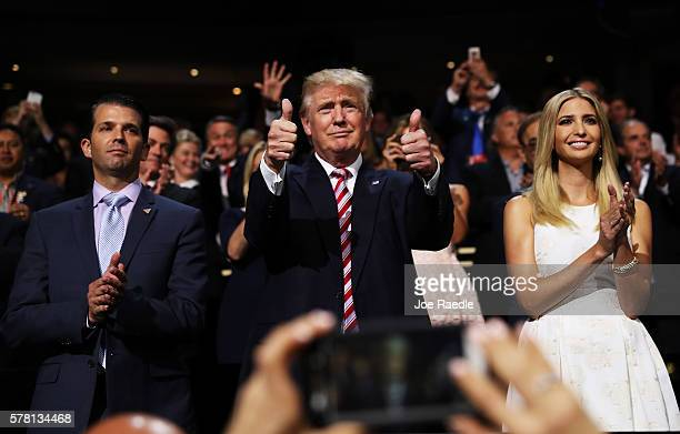 Republican presidential candidate Donald Trump gives two thumbs up as Donald Trump Jr. And Ivanka Trump stand and cheer for Eric Trump as he delivers...