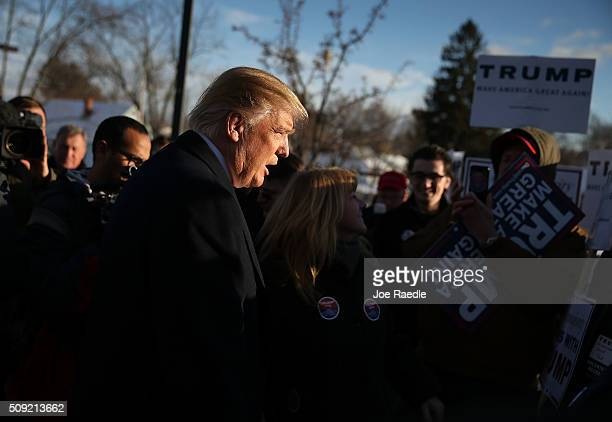 Republican presidential candidate Donald Trump greets people as he visits a polling station as voters cast their primary day ballots on February 9...
