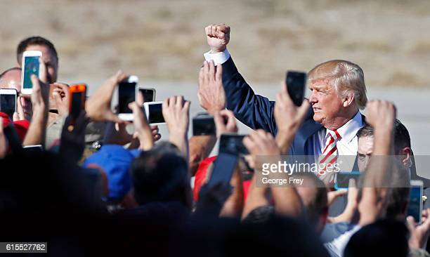 Republican presidential candidate Donald Trump greets supporters as he arrives to speak at a rally at Grand Junction Regional Airport on October 18...
