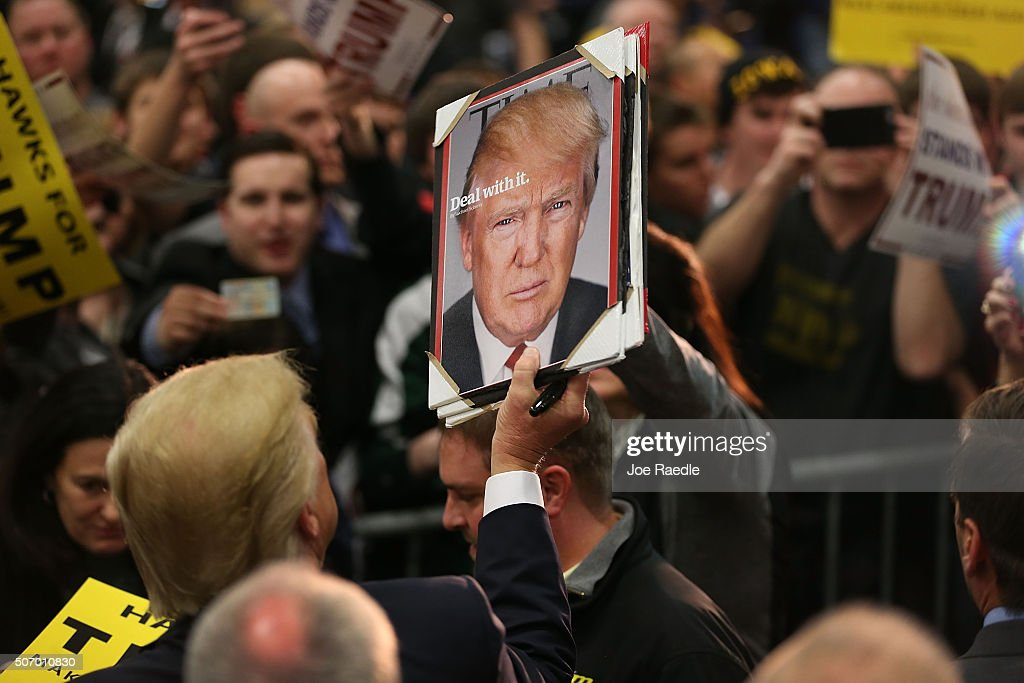 Republican presidential candidate Donald Trump holds a picture of himself after being given it as he greets people during a campaign event at the University of Iowa on January 26, 2016 in Iowa City, Iowa. Trump continues his quest to become the Republican presidential nominee.