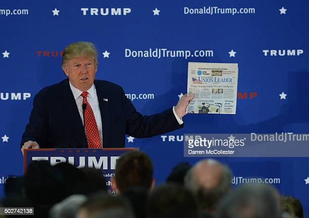 Republican Presidential candidate Donald Trump holds up a copy of the Manchester Union Leader at a rally at Pennichuck Middle School December 28 2015...