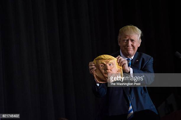 Republican presidential candidate Donald Trump holds up a mask depicting himself as he speaks during a campaign event at Robarts Arena at the...