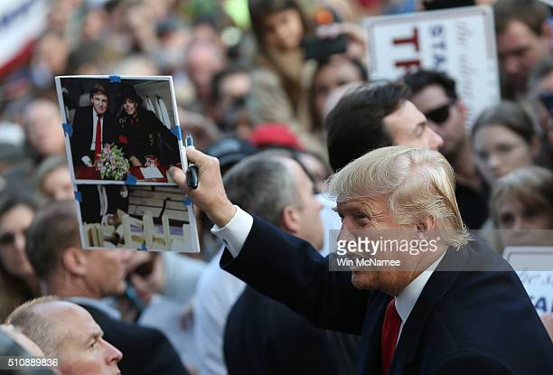 Republican presidential candidate Donald Trump holds up a photo of himself with pop star Michael Jackson that a member of the audience asked him to...