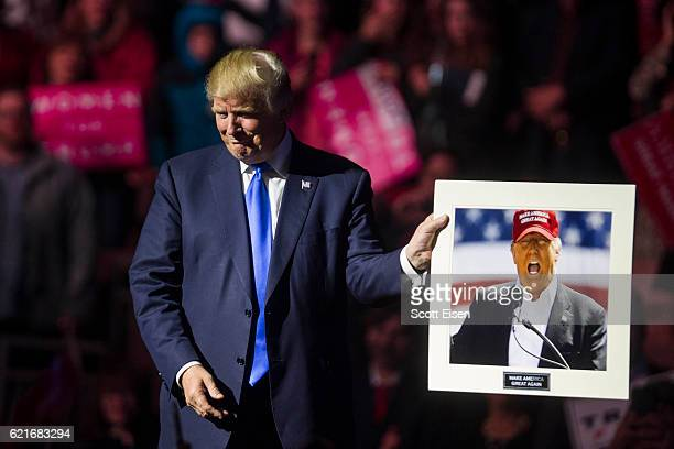 Republican presidential candidate Donald Trump holds up a picture of himself that supporter handed him at the end of his rally at the SNHU Arena on...