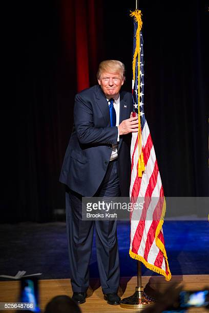Republican presidential candidate Donald Trump hugs an American flag while attending a town hall in Derry NH