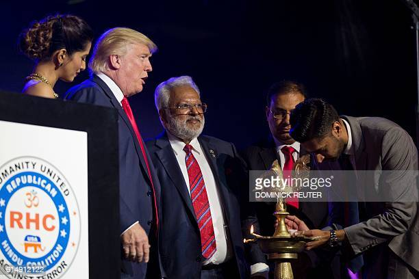 Republican presidential candidate Donald Trump joins in the lighting of a ceremonial diva candle during a Hindu political organization's antiterror...