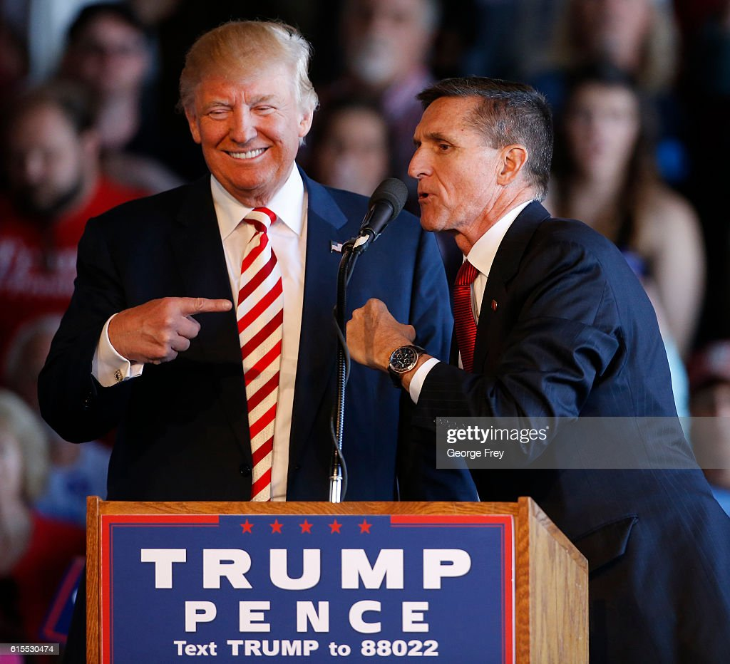 Republican presidential candidate Donald Trump (L) jokes with retired Gen. Michael Flynn as they speak at a rally at Grand Junction Regional Airport on October 18, 2016 in Grand Junction Colorado. Trump is on his way to Las Vegas for the third and final presidential debate against Democratic rival Hillary Clinton.