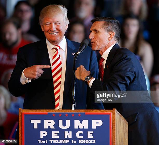 Republican presidential candidate Donald Trump jokes with retired Gen Michael Flynn as they speak at a rally at Grand Junction Regional Airport on...