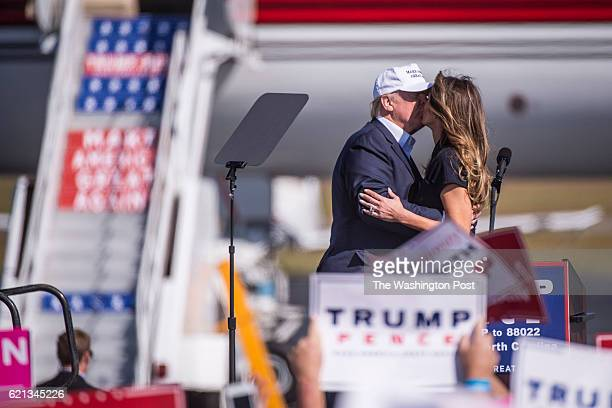 Republican presidential candidate Donald Trump kisses his wife Melania Trump as they speak during a campaign event at the Wilmington International...